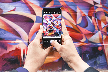 person-taking-a-photo-of-graffiti-wall-art